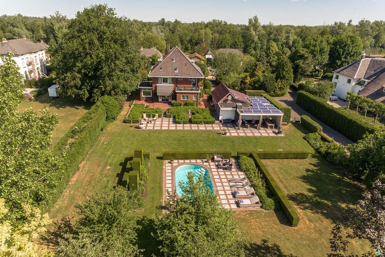 villa met een grote achtertuin en een zwembad