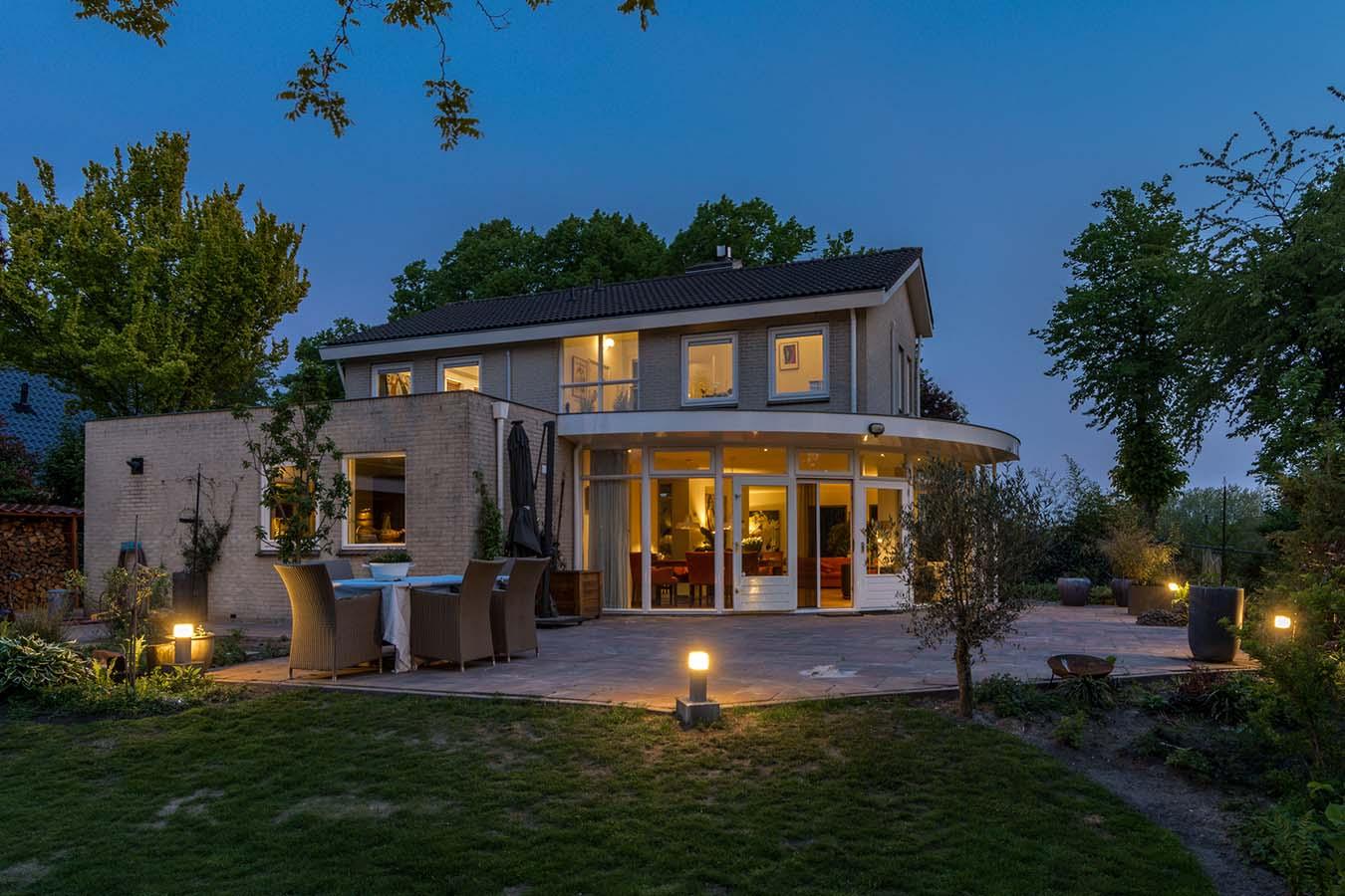 avondfoto van een woning en de achtertuin