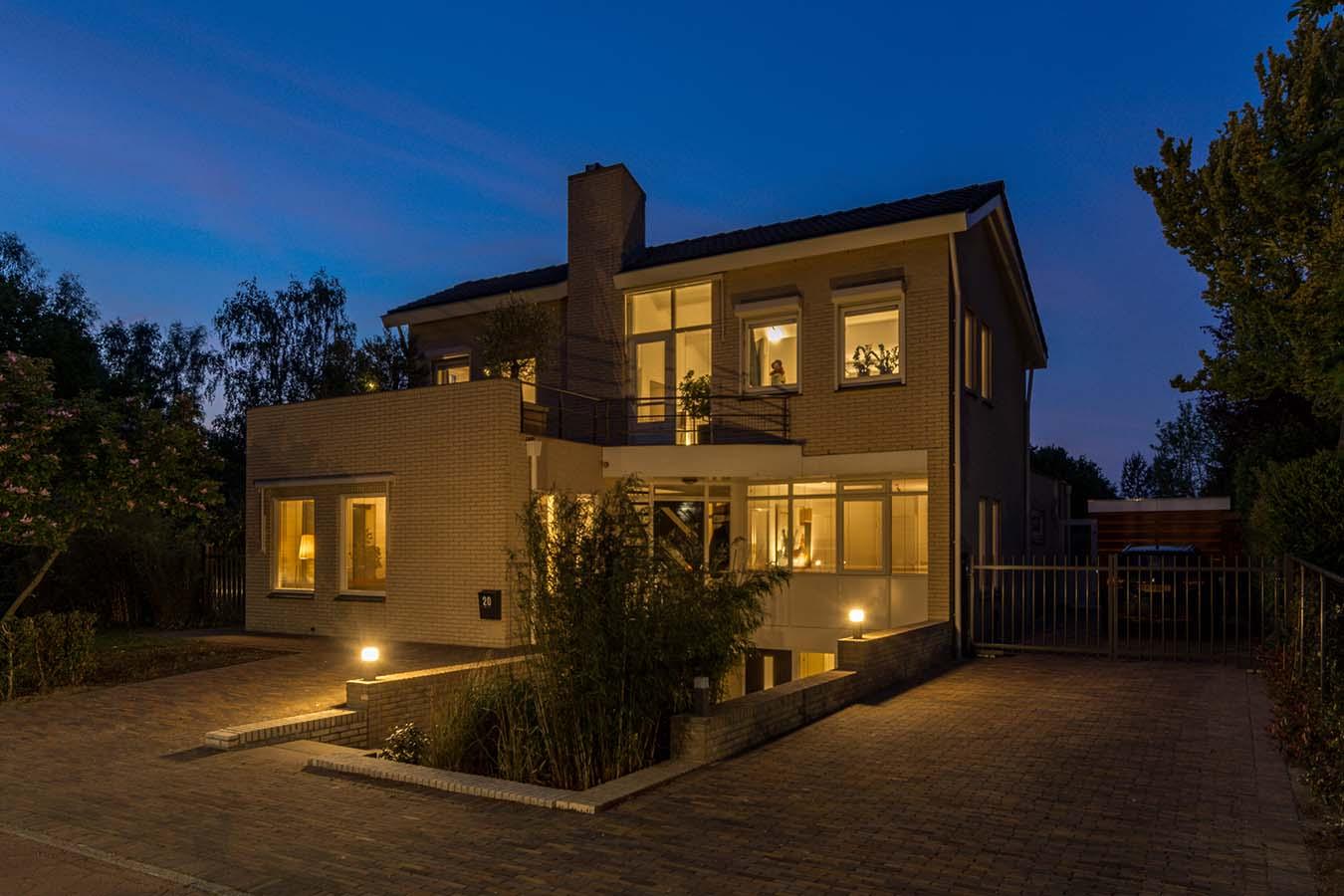 avondfoto van een woning met een lagere verdieping