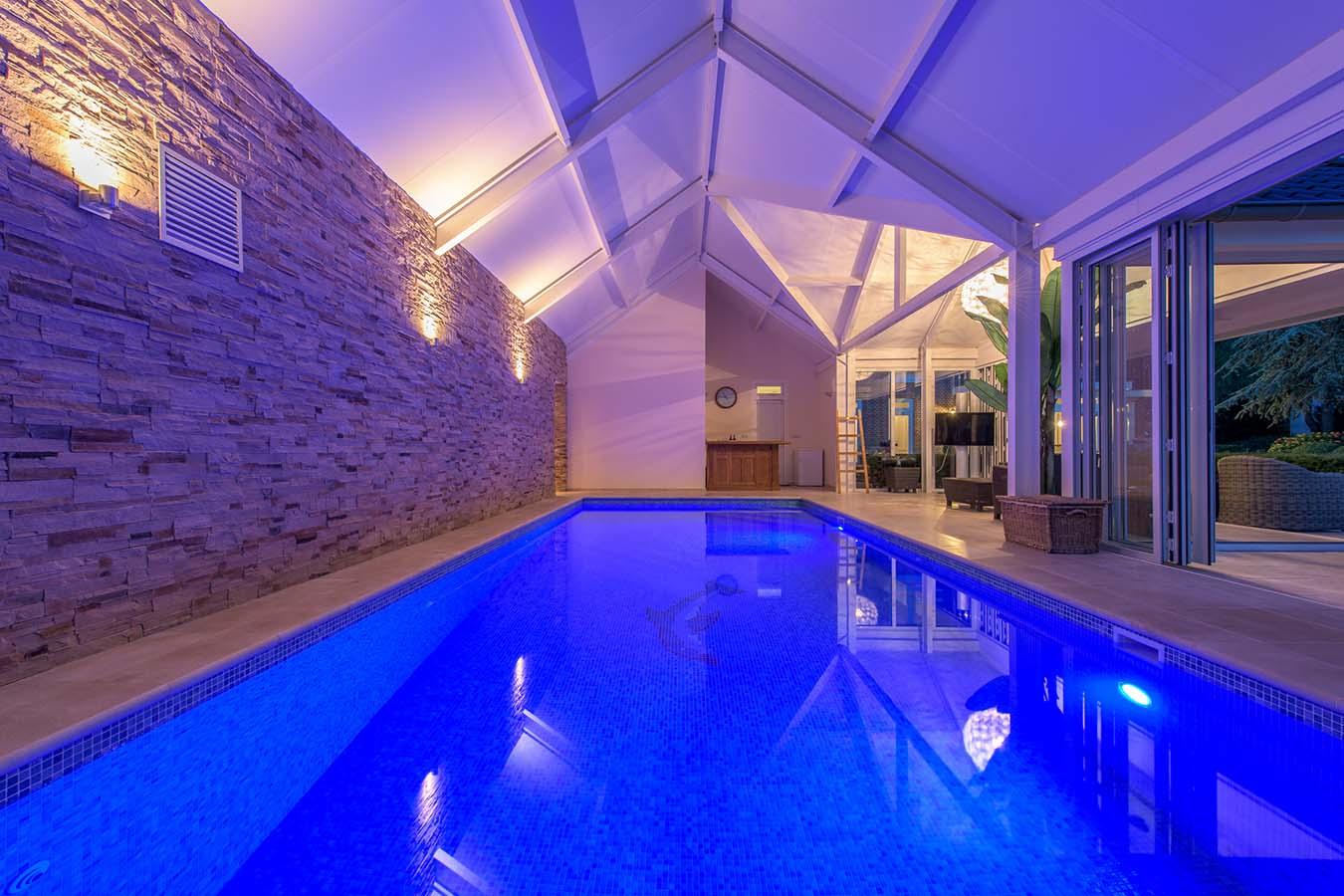 zwembad met blauw licht en uitzicht naar buiten